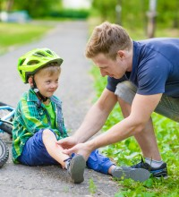 father putting an aid on young boy's injury who fell off his bicycle.